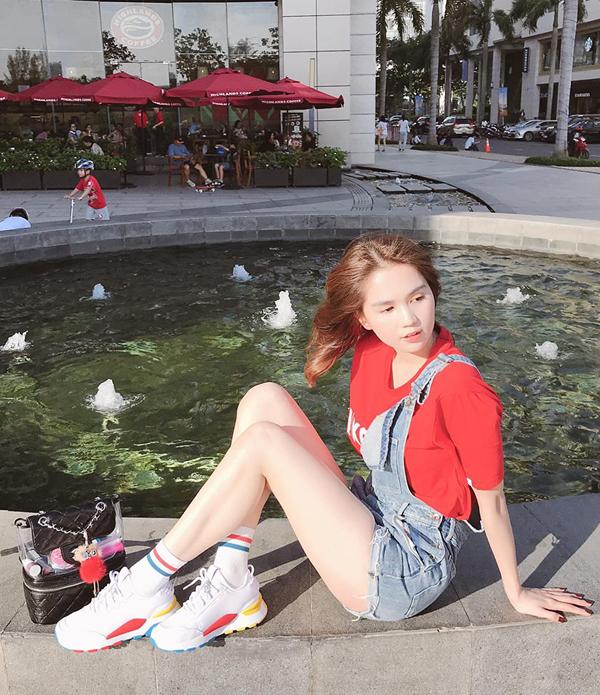 Ngọc Trinh giúp mình thoải mái trong mùa nóng với cách phối yếm, áo thun, giầy sneaker và ba lô phối nhựa trong.