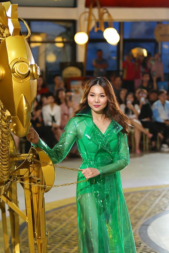 Siêu mẫu gây ấn tượng với trang phục body suit tông màu và áo khoác trên chất liệu nhựa trong.