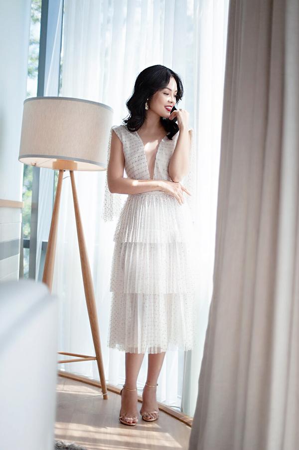 Nét điệu đà con gái được thể rõ qua cách phối hợp chất liệu vải chấm bi kim tuyến cùng dáng váy xếp tầng.