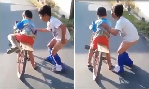 Cậu bé bị tụt quần vì mải mê tập xe đạp cho em trai