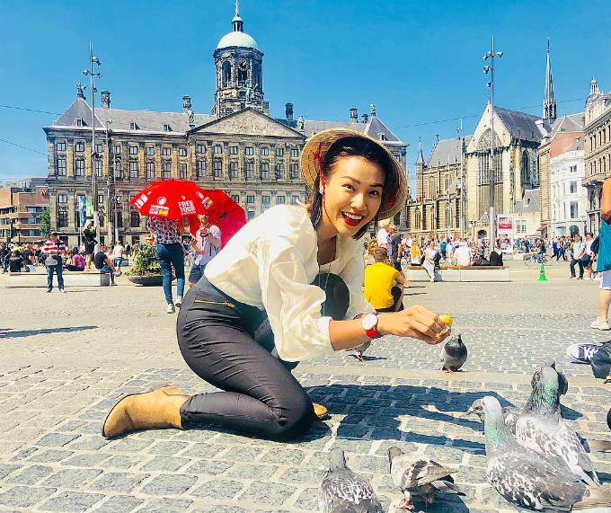 MC Hoàng Oanh cho chim bồ câu ăn trong chuyến du lịch ở Hà Lan.