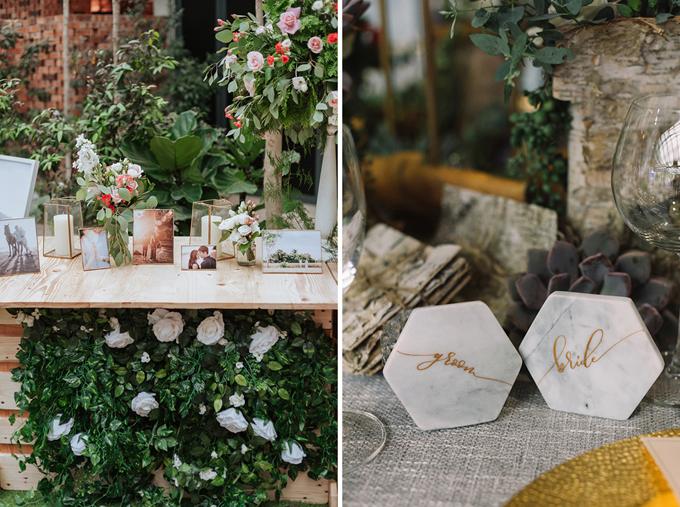 Quầy tiếp tân đám cưới được tô điểm bởi ảnh cưới của hai vợ chồng, nến cốc và những lọ hoa hồng tươi.