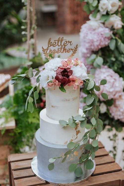 Bánh cưới ba tầng của uyên ương được trang trí bởi dòng thông điệp Better together (tạm dịch: Trở nên tốt hơn cùng nhau)được mạ vàng. Sự xuất hiện của những bông hoa rực rỡ tông đỏ tía, hồng nhạt trên bánh cưới sẽ giúp bữa tiệc thêm ngọt ngào và lãng mạn.