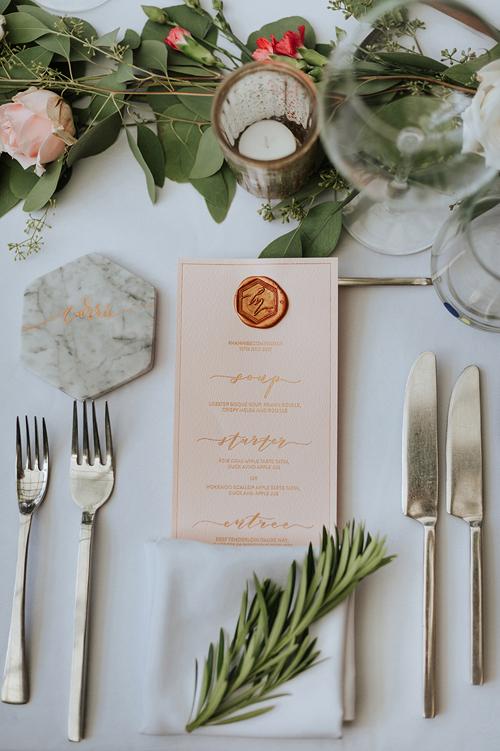 Tờ thực đơn docô dâutay thiết kế. Uyên ương cũng tựđóng dấu sáp với chữ cái đầu trong tên hai vợ chồng.