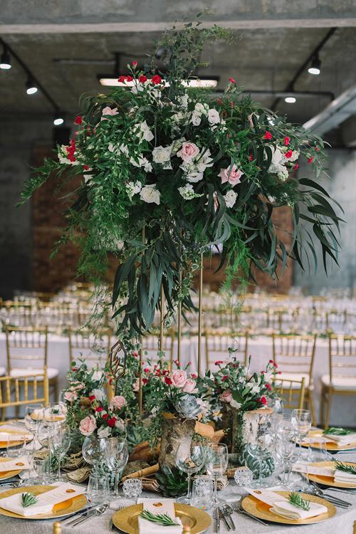 Bàn tiệc dành cho cô dâu chú rể và cha mẹ đôi bên được trang trí bởi trụ hoa cao và những khóm hoa hồng nhỏ xinh bên dưới.