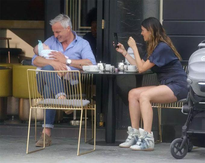 Gia đình ba người vui đùa, chụp ảnh cho nhau trong quán café.