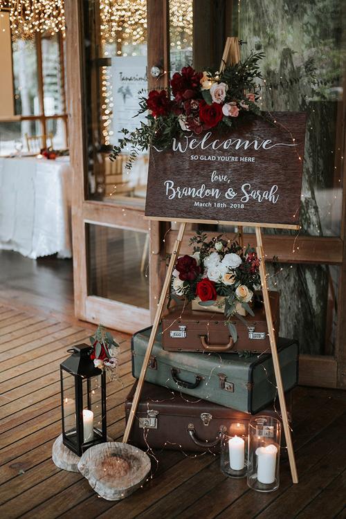 Bảng thông báo tiệc cưới được tô điểm bởi hoa hồng tươi, mẫu đơn và lá cây. Cặp vợ chồng xếpnhiều vali, đặt thêmnến trắng để trang trí.