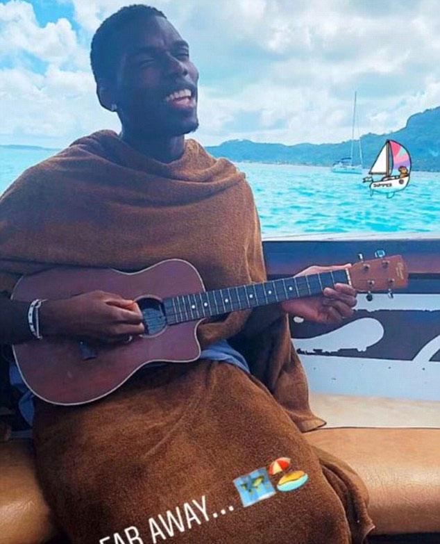 Pogba quấn khăn, biểu diễn đàn nhỏ ukulele khi ngồi trên du thuyền.