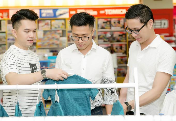 Ca sĩ Nam Cường (trái) và MC Quốc Bình (giữa) chọn trang phục cho con. MC Anh Quân cũng tham gia sự kiện này.