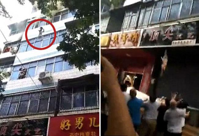 Hai đứa trẻ rơi từ trên cửa sổ xuống nhưng không hề hấn gì sau trận hoả hoạn sáng 3/8 ở tỉnh Hà Nam, Trung Quốc. Ảnh cắt từ video.