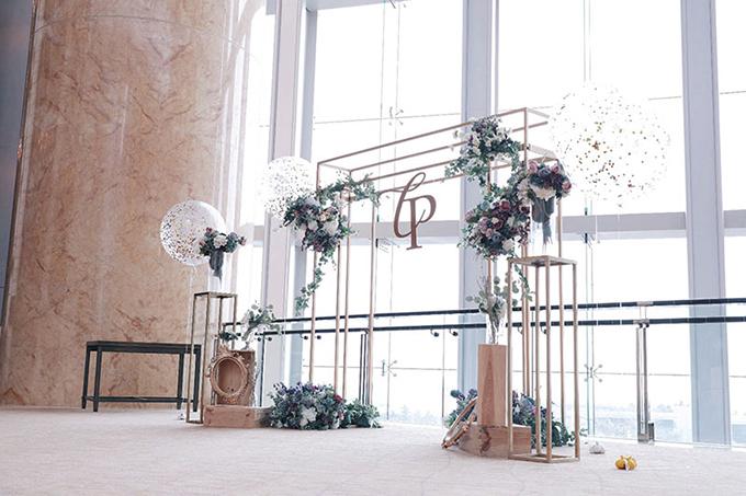Một cách để tạo nên điểm nhấn cho đám cưới trong nhà là dựng khung kim loại mạ vàng và kết hoa tươi bên cạnh. Các chi tiết mạ vàng phù hợp với không gian sảnh tiệc rộng, đem đến vẻ sang trọng.