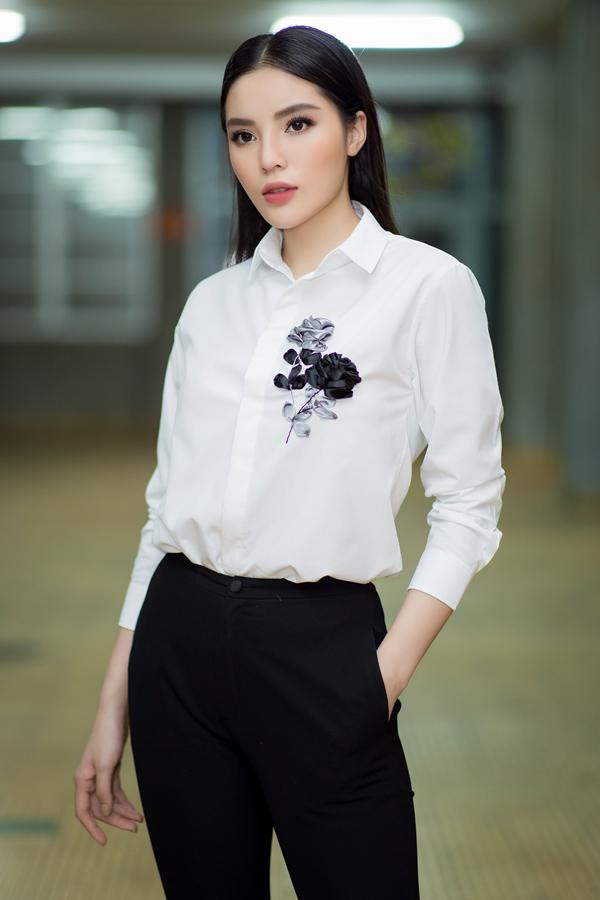 Hoa hậu Việt Nam 2014 trông giản dị, thanh lịch khi diện áo sơmi trắng thêu hoa hồng, quần tây ống loe.