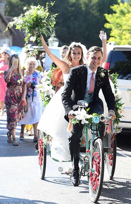 Chú rểVan Straubenzee lái chiếc xe ba bánh chở cô dâu xinh đẹp Daisy Jenks ra khỏi nhà thờ sau khi làm lễ.