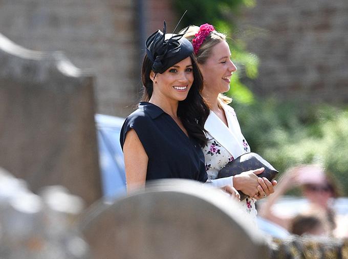 Meghan mặc một chiếc váy màu xanh navy sẫm, phần chân váy xếp ly mềm mại và phối giữa ba màu trắng, hồng và xanh. Cô hoàn thiện bộ trang phục với mũ đội đầu, ví cầm tay và giày cao gót màu đen.