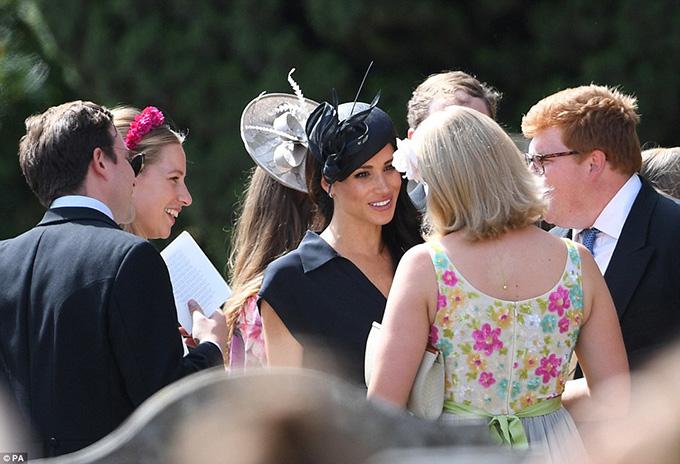 Meghan một mình vui vẻ trò chuyện với các khách mời do hoàng tử Harry đang bận rộn với vai trò phù rể.
