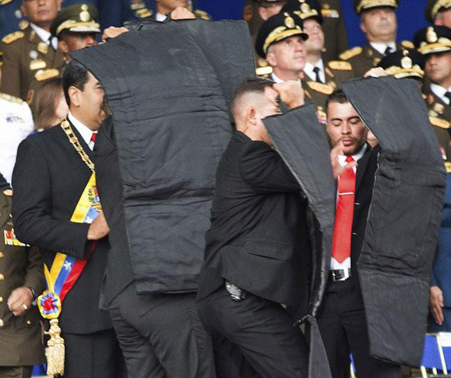 Lực lượng bảo vệ riêng cho tổng thống che chắn kỹ càng khi nghi ông Maduro bị ám sát lúc đangphát biểu kỷ niệm 81 năm ngày thành lập Lực lượng Phòng vệ quốc gia hôm 4/8. Ảnh: AP.