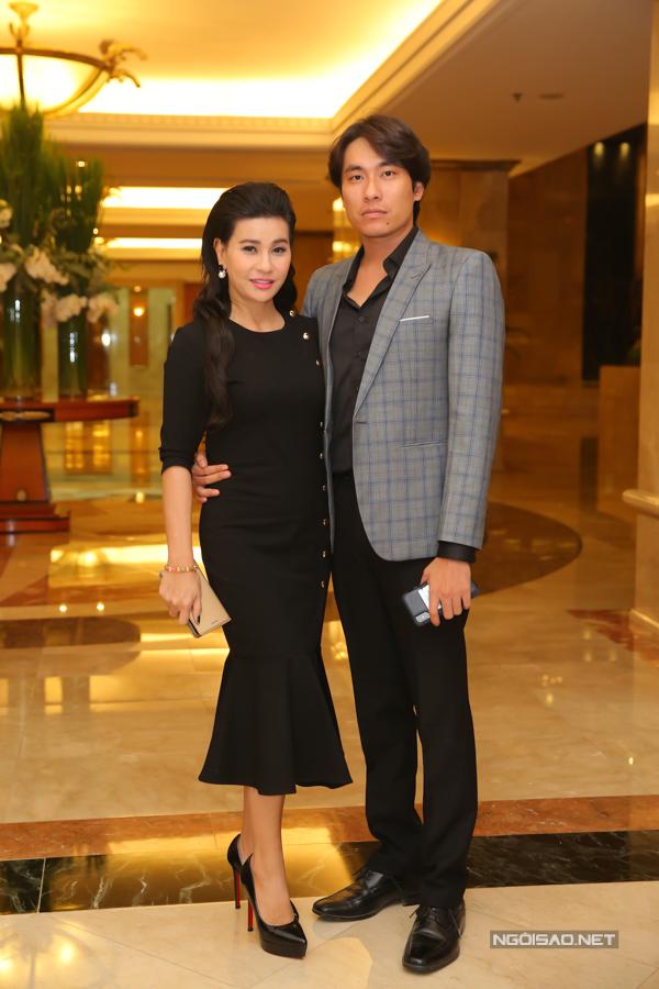Kiều Minh Tuấn ôm eo bà xã Cát Phượng chụp ảnh trước khi vào phòng tiệc.