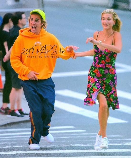 Justin Bieber và Hailey Baldwin tung tăng chạy qua đường ở New York hôm thứ hai, 6/8. Giọng ca Baby không chỉ gây chú ý vì gương mặt nổi tiếng của anh mà còn bởi bộ trang phục sắc màu chói lóa giữa phố. Trong khi vị hôn thê diện váy hè sexy, Bieber lại mặc đồ thun kín mít, rộng thùng thình và xỏ xép lê của khách sạn ra đường.