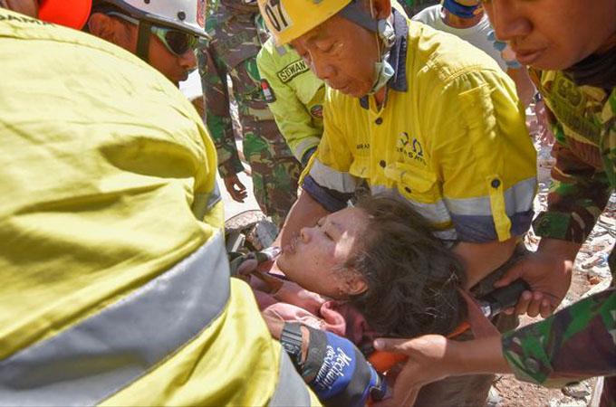 Nadia Revanale được cáng đi sau khi được cứu hộ kéo lên từ dưới đống đổ nát. Ảnh: Mirror.