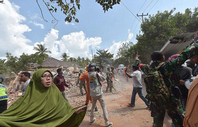 Binh lính Indonesia trấn an người dân sau cơn dư chấn sáng nay. Ảnh: AFP.