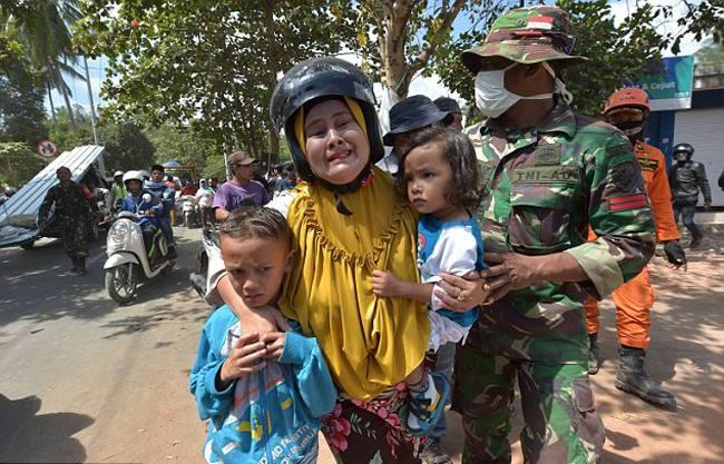 Một phụ nữ ôm con nhỏ khóc khi cơn dư chấn xảy ra ởLombok. Ảnh: AFP.