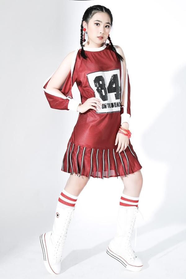 Kiểu áo cánh dơi xẻ tai tạo sự thuận tiện cho các bé tham gia hoạt động thể thao. Hai gam màu đỏ - trắng cũng được kết hợp khéo léo qua các chi tiết điểm nhấn đan xen giữa váy và giày thể thao.