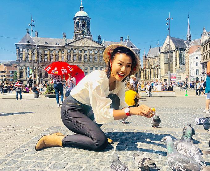 Á hậu hào hứng cho bồ câu ăn trên quảng trường Dam Square.