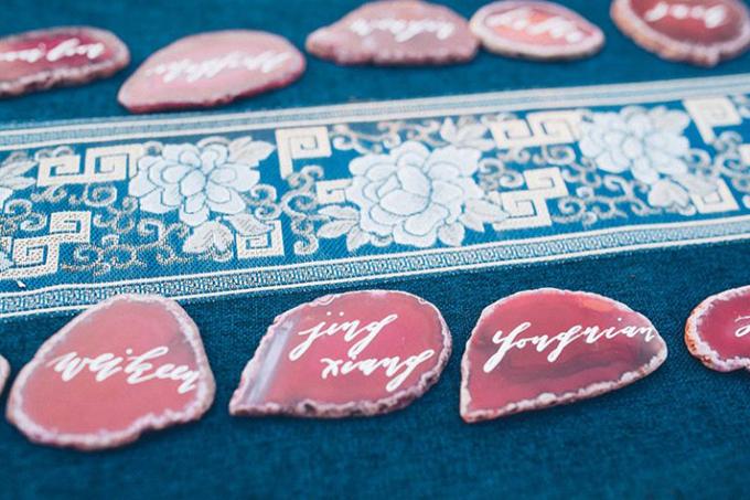 Cặp vợ chồng viết tên khách mời lên phiến đá nhỏ có màu đỏ trầm. Sự tương phản giữa xanh lam và đỏ burgundy không quá gay gắt do cósự kết hợp của màu trắng trung tính đến từ họa tiết trên khăn trải bàn.