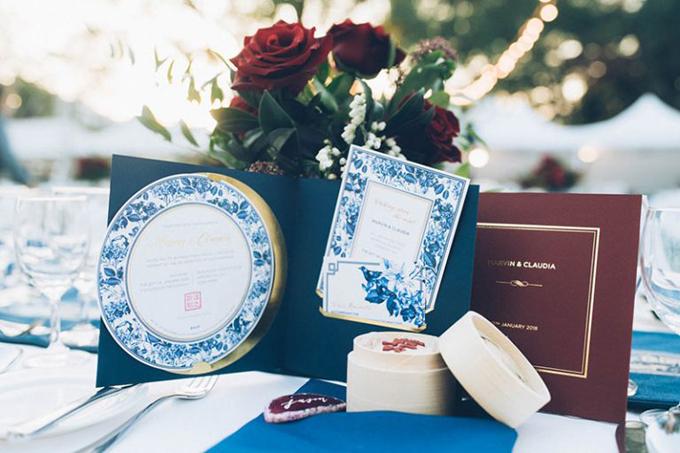 Ngoài màu chủ đạo là đỏ burgundy, cặp vợ chồng chọn màu xanh lam để trang trí tiệc cưới. Hoa văn trên đĩa ăn và họa tiết của tờ thực đơnhoàn toàn trùng khớp, tạo sự đồng điệu cho không gian tiệc cưới.