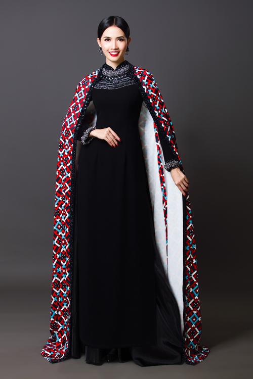 Áo dài đen trầm lắng được đính cườm và đáở ngực và viền tay áo. Hoa hậu Phan Thị Mơ kết hợp áo choàng dài có họa tiết hình học màu xanh, đỏ, trắng tạo sự sinh động cho tổng thể trang phục.