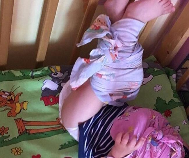 Nhà trẻ ác quỷ đang bị điều tra vì trói chân tay trẻ em vào cũi ở Nga - 1