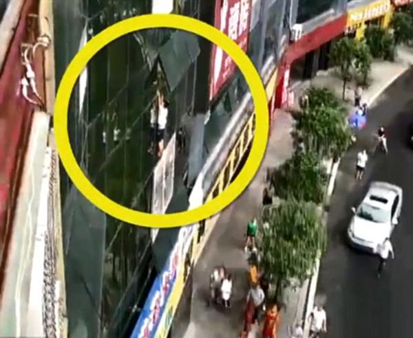 Bé trai 7 tuổi cố bám vào mép kính cửa sổ trước khi rơi xuống. Ảnh: Pear Video.