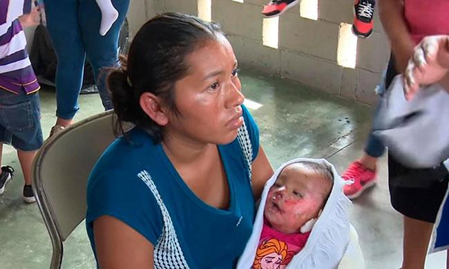 Mẹ của bé gái bế con trên tay tại nhà thờ ở San Perdo Sula.  Ảnh: Central Europan News.