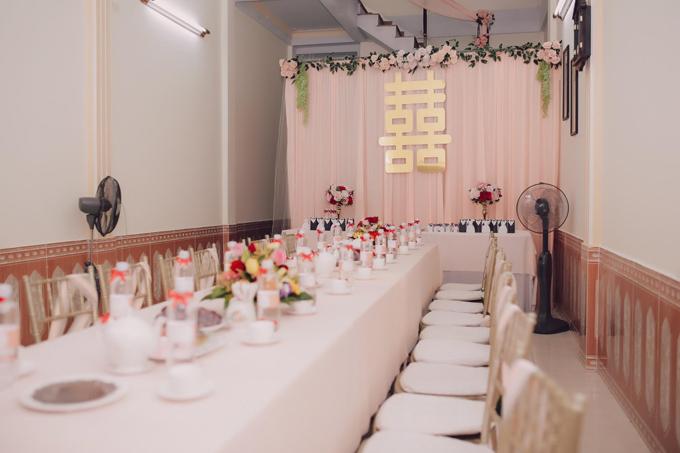 Toàn bộ đồ đạc trong phòng khách của gia đình được dọn lại để nhường chỗ bày bàn tiệc ngọt. Nữ tiếp viên hàng không kết hợp chữ hỷ to bản màu vàng đồng đặt trên nền phông cưới bằng lụa màu cam nhạt. Hoa tươi kết hợp với hoa lụa cỡ lớn được dùng làm điểm nhấn.