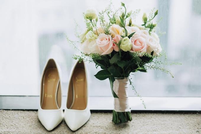 Bó hoa cưới của cô cũng trung thành với tông màu cam, hồng nhạtvà được kết từ các loại hoa dễ tìm ở Việt Nam như hồng, cát tường... Diệu Thúy hoàn thiện vẻ ngoài bằng giày cao gót mũi nhọn màu trắng của nhà mốt Christian Louboutin.