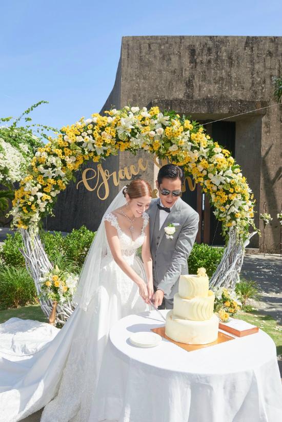 Không gian lễ cưới được decor với hai màu vàng, trắng, xen lẫn sắc trời mây xanh thẳm, tạo nên khung cảnh thiên đường. Lễ đường còn có cổng hoa, kết tên của cặp đôi bằng tiếng Anh Grace & Kevin.