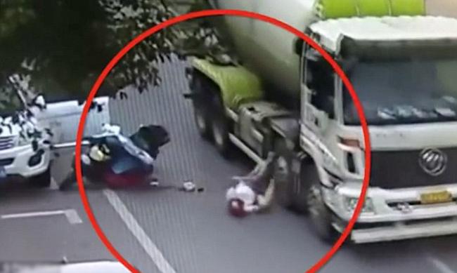 Nạn nhân đi xe máy đội mũ bảo hiểm bị ngã ra đường do chiếc xe hơi màu trắng bất ngờ mở cửa ở tỉnh Chiết Giang, Trung Quốc hôm 7/8. Ảnh: Pear Video.