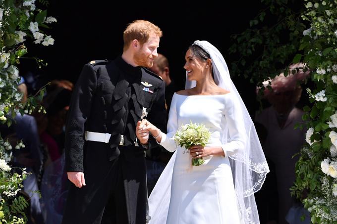 Meghan và Hoàng tử Harry đứng trước nhà nguyện St. Geoger sau khi hôn lễ hôm 19/5 kết thúc. Ảnh: UK Press.