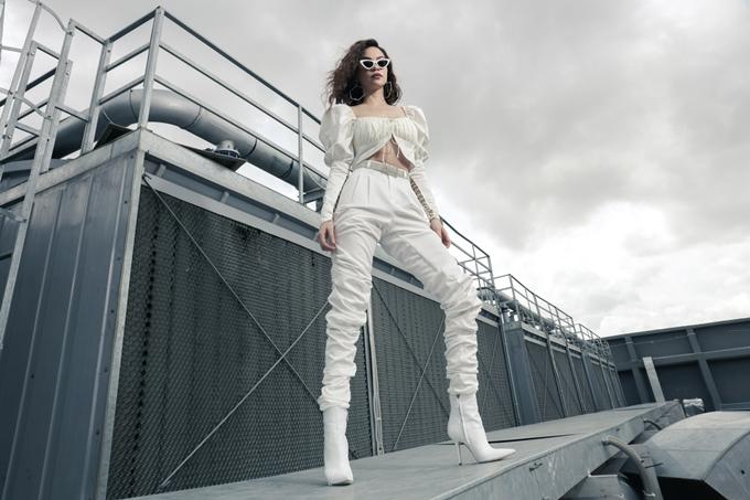 Nữ ca sĩ diện nguyên set đồ màu trắng, tạo dáng mạnh mẽ trên tầng thượng một tòa nhà.