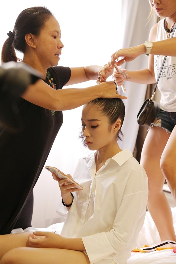 Mọi người đều hối hả làm việc. Trong lúc làm tóc, cô bé Thanh Hàtranh thủ xem lại đường dây và thứ tự trình diễn.
