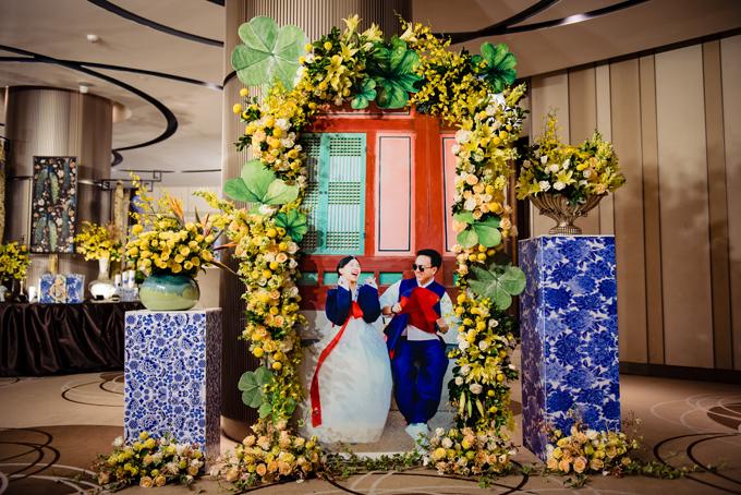 Ảnh cưới của uyên ương được đặt bên ngoài sảnh tiệc với sự xuất hiện của cỏ bốn lá, hoa hồng trắng, vàng và hoa thiên điểu.