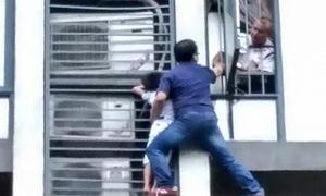 Ông bố tay không trèo ra ngoài cửa sổ tầng 7 cứu con