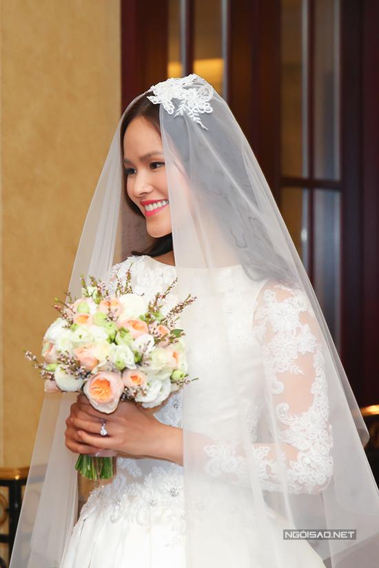 Tuyết Lan chọn kiểu váy cưới trang nhã, tóc uốn sóng nhẹ nhàng khi cùng chồng ra đón khách.