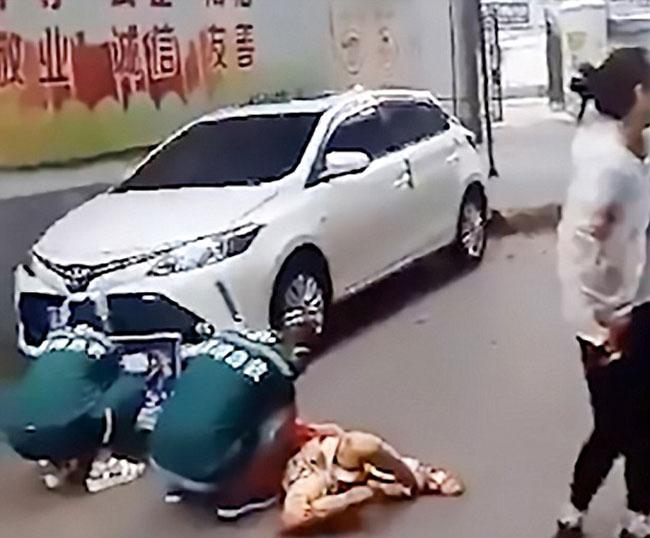 Các nhân viên y tế đến hiện trường thăm khám sơ bộ cho bé trai ở Hồ Nam, Trung Quốcbị chậu hoa rơi vào đầu trước khi đưa cậu bé đến bệnh viện hôm 16/8. Ảnh: AsiaWire.