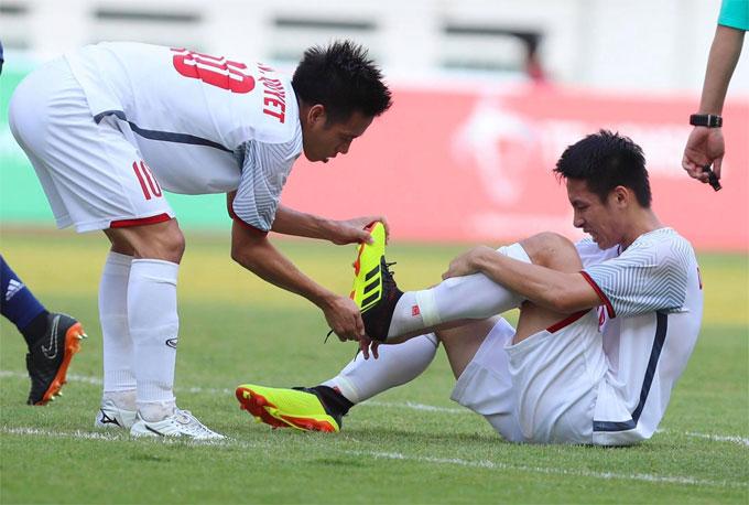 ... cởi giày cho đồng đội để bớt đau. Hai cầu thủ Việt Nam đang cùng thi đấu trong màu áo CLB Hà Nội.