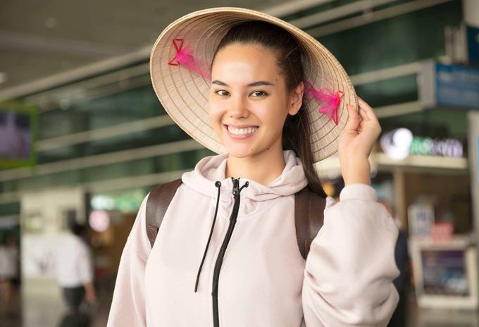 Catriona Gray rất thích thú với món quà là chiếc nón lá, bó hoa sen do cô bạn thân người Việttặng.
