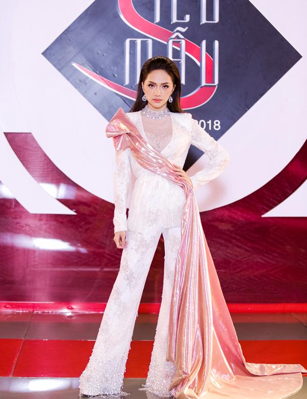Hoa hậu Hương Giang sẽ trở nên hấp dẫn hơn nếu lược bỏ phần vải bắt sáng dài thượt, hoàn toàn lạc quẻ trên bộ suit trắng.
