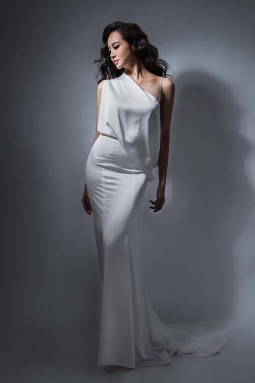 Mẫu váy dáng sheath lệch vai giúp nàng dâu hóa thân thành nữ thần Hy Lạp trong câu chuyện cổ. Thông qua thời trang ngày cưới, nàng dâu có thể bộc lộ phong cách, cá tính cũng như gu thẩm mỹ của mình.