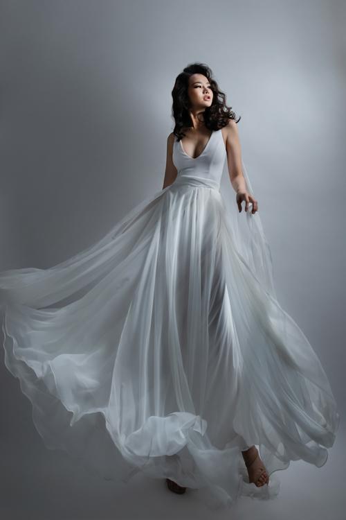 Phom váy A-line mang nét nhẹ nhàng, bay bổngsẽ đem đếncho cô dâu vẻ đẹp mỏng manhtựa sương mai. Thiết kế cổ chữ V xẻ ngực sâu sẽ giúp nàng thêm quyến rũ, gợi cảm trong đôi mắt của đức lang quân.