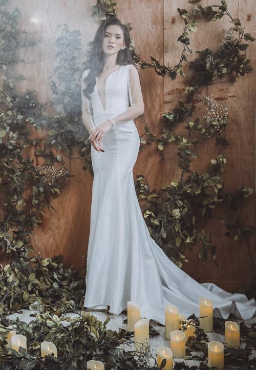 Váy cưới trơn tưởng chừng đơn giản nhưng không vì thế mà mất đi nét nổi bật, sự quyến rũ. Nhờ thiết kế cổ chữ V xẻ ngực sâu và phần xòe nhẹ bắt đầu từ ngang đùi, váy giúp tôn lên đường cong của người mặc.